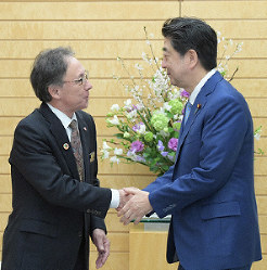Prime Minister Shinzo Abe, right, shakes hands with Okinawa Gov. Denny Tamaki at the prime minister's office in Tokyo on March 19, 2019. (Mainichi/Masahiro Kawata)