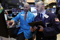Specialist Meric Greenbaum, left, and trader Fred DeMarco work on the floor of the New York Stock Exchange, on March 18, 2019. (AP Photo/Richard Drew)