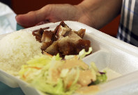 In this March 14, 2019 photo, Belinda Lau, manager of the Wiki Wiki Drive Inn takeout restaurant in Honolulu, holds a polystyrene foam box containing an order of roast pork, rice and salad. (AP Photo/Audrey McAvoy)
