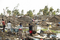 In March 15, 2019 photo provided by the International Red Cross, people try to salvage what is left of their homes after Tropical Cyclone Idai, in Beira, Mozambique. (Denis Onyodi/IFRC via AP)