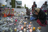 People mourn at a makeshift memorial site near the Al Noor mosque in Christchurch, New Zealand, on March 19, 2019. (AP Photo/Vincent Thian)