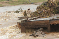 A man stands on the edge of a collapsed bridge in Chimanimani, about 600 kilometers southeast of Harare, Zimbabwe, on March 18, 2019. (AP Photo/Tsvangirayi Mukwazhi)