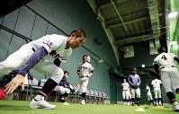 室内練習場で調整する山梨学院の選手たち=阪神甲子園球場で2019年3月19日、幾島健太郎撮影