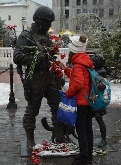 広場を通りかかった少女はバラの花を置き直した。銅像はクリミアの住民からロシア兵への感謝を表す狙いで建てられた=クリミアのシンフェロポリで2019年2月27日、大前仁撮影