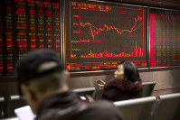 Chinese investors monitor stock prices at a brokerage house in Beijing, on March 20, 2019. (AP Photo/Mark Schiefelbein)