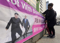 A woman displays a banner showing a photo of North Korean leader Kim Jong Un and South Korean President Moon Jae-in, right, to wish for peace on the Korean Peninsula, in Seoul, South Korea, on March 19, 2019. (AP Photo/Ahn Young-joon)