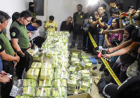 In this March 19, 2019 photo provided by the Philippine Drug Enforcement Agency (PDEA), Aaron Aquino, second from left, chief of PDEA, looks at more than 160 kilograms (353 pounds) of methamphetamine drugs concealed in tea wrappers following
