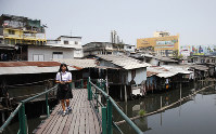 In this March 19, 2019 photo, Thai student walks over a footbridge through dilapidated homes along the Phra Khanong canal in Bangkok, Thailand. (AP Photo/Sakchai Lalit)