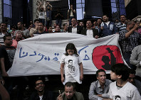 In this May 3, 2016 file photo, a girl stands in front of a banner with Arabic that reads,