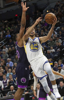 Golden State Warriors' Stephen Curry, right, lays up as Minnesota Timberwolves' Josh Okogie defends in the second half of an NBA basketball game March 19, 2019, in Minneapolis. The Warriors won 117-107. (AP Photo/Jim Mone)