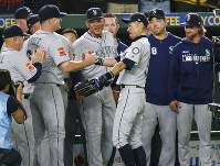Seattle Mariners right fielder Ichiro Suzuki, third from right, is applauded by teammates while leaving the field for defensive substitution in the eighth inning of Game 2 of the Major League baseball opening series against the Oakland Athletics at Tokyo Dome in Tokyo, Thursday, March 21, 2019. (AP Photo/Koji Sasahara)