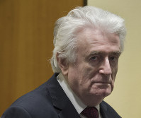 Former Bosnian Serb leader Radovan Karadzic enters the court room of the International Residual Mechanism for Criminal Tribunals in The Hague, Netherlands, on March 20, 2019. (AP Photo/Peter Dejong, Pool)