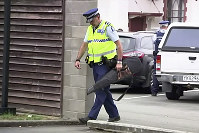 In this image made from video taken on March 19, 2019, a police officer carries a gun voluntarily surrendered by a member of the public into the Masterton police station in Masterton, New Zealand. (TVNZ via AP)