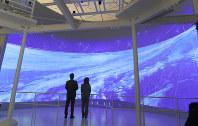 巨大なスクリーンに映し出されたニュートリノが飛来する様子を紹介する映像=飛騨市神岡町夕陽ケ丘の「ひだ宇宙科学館カミオカラボ」で