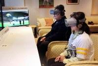 VRのゴーグルを装着し、試合の3Dパノラマ映像を体験する参加者たち。奥のモニターに映った映像が、ゴーグル内でみられる=福岡市のヤフオクドームで21日午後