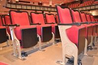 開館当初のデザインが復活した大ホール客席の椅子。名古屋市章の「まる八」もデザインされている=2019年3月22日9時41分、山田泰生撮影