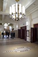 1階広間天井につるされたシャンデリアはLED化され、床にはモザイクタイルが組み込まれている=名古屋市昭和区の市公会堂で2019年3月22日11時9分、山田泰生撮影
