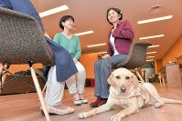 Sea Mari, right, accompanied by her guide dog, talks with female participants at MOFCA in Tokyo's Chiyoda Ward, on March 30, 2019. (Mainichi/Emi Naito)