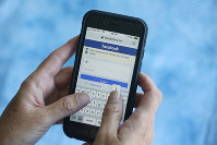 In this Aug. 21, 2018, file photo a Facebook start page is shown on a smartphone in Surfside, Fla. (AP Photo/Wilfredo Lee)