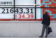 A man looks at an electronic stock board showing Japan's Nikkei 225 index at a securities firm in Tokyo, on March 22, 2019. (AP Photo/Eugene Hoshiko)