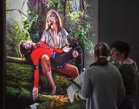 Visitors talk about the picture 'American Jesus: Hold me, carry me boldly' from US artist David LaChapelle at a preview of the exhibition 'Michael Jackson: On The Wall' at the Bundeskunsthalle museum in Bonn, Germany, on March 21, 2019. (AP Photo/Martin Meissner)