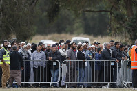 Mourners attend the service for a victim of the mosque shootings for a burial at the Memorial Park Cemetery in Christchurch, New Zealand, on March 22, 2019. (AP Photo/Vincent Thian)