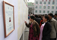 People inspect the list of voters as portrait of a candidate for the national legislature is displayed on the left, during the election at a polling station in Pyongyang, North Korea, on March 10, 2019. (AP Photo/Dita Alangkara)
