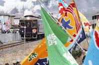 大漁旗を振る住民らに出迎えられ、磯鶏駅に到着した三陸鉄道「リアス線」の記念列車=岩手県宮古市で2019年3月23日、喜屋武真之介撮影