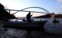 気仙沼大島大橋のそばで、手こぎで船を片付ける小松達雄さん(73)。祖父から引き継いだ漁場は車の入れない細い山道を下った先にあり、小松さんは15年以上前に遠洋漁業を引退した後、この小さな浜でただ一人、ワカメやコンブなどの養殖を続けてきた。「後継ぎはいない。俺の代で終わりだ」=3月