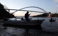気仙沼大島大橋のそばで、手こぎで船を片付ける小松達雄さん(73)。祖父から引き継いだ漁場は車の入れない細い山道を下った先にあり、小松さんは15年以上前に遠洋漁業を引退した後、この小さな浜でただ一人、ワカメやコンブなどの養殖を続けてきた。「後継ぎはいない。俺の代で終わりだ」=宮城県気仙沼市の大島で2019年3月19日、喜屋武真之介撮影
