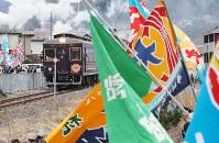 磯鶏駅に到着した三陸鉄道リアス線の記念列車を出迎える大漁旗を手にした住民たち=岩手県宮古市で2019年3月23日午後1時19分、喜屋武真之介撮影