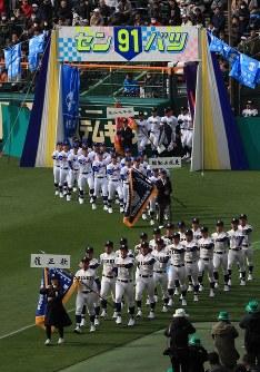 入場行進する履正社(手前)など近畿ブロックの選手たち=阪神甲子園球場で2019年3月23日、玉城達郎撮影