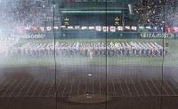花火の白煙の中、一斉行進する各校の選手たち=阪神甲子園球場で2019年3月23日、中村真一郎撮影