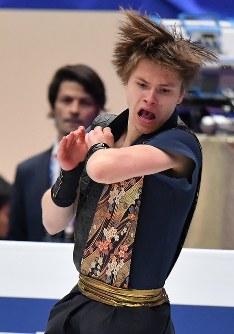 男子フリーで演技するラトビアのデニス・ヴァシリエフス。奥は見守るランビエ-ルコーチ=さいたまスーパーアリーナで2019年3月23日、宮間俊樹撮影