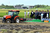 This file photo taken on Sept. 5, 2018 shows Prime Minister Shinzo Abe inspecting a self-driving tractor at Lawson Farm Niigata in the city of Niigata. (Pool photo)