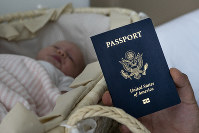 In this photo taken on Jan. 24, 2019, Denis Wolok, the father of 1-month-old Eva, shows the child's U.S. passport during an interview with The Associated Press in Hollywood, Fla. (AP Photo/Iuliia Stashevska)