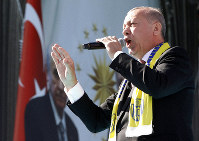 Turkey's President Recep Tayyip Erdogan sings a political song before his address to the supporters of his ruling Justice and Development Party, AKP, during a rally in Ankara, Turkey, Saturday, March 23, 2019, ahead of local elections scheduled for March 31, 2019. (AP Photo/Burhan Ozbilici)