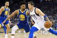 Dallas Mavericks forward Luka Doncic, right, dribbles as Golden State Warriors guard Quinn Cook (4) defends in the first half of an NBA basketball game Saturday, March 23, 2019, in Oakland, Calif. (AP Photo/John Hefti)