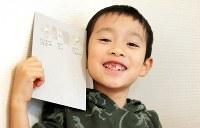 東京都内に住む7歳の男の子。乳歯を貼り付けた紙には、抜けたときの年齢が書き込まれていた=家族提供