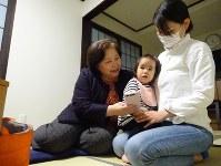 孫の一香ちゃんをあやす佐藤真弓さん(左)