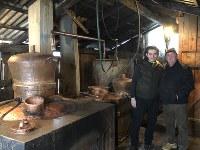 パウル・イリエシュさん(左)が所有するツイカの蒸留所。ペートル・ボボチャさん(右)ら多くの村人がツイカ造りに利用するルーマニア北西部ポイエニレイゼイ村で2019年1月22日、三木幸治撮影