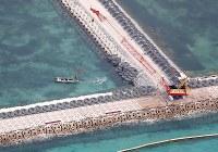米軍普天間飛行場の移設工事が進み、新たな区域(左)で作業するクレーン車=沖縄県名護市で2019年3月25日午前10時、本社機「希望」から佐々木順一撮影