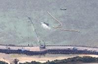 米軍普天間飛行場の移設工事が進み、新たな区域で作業するクレーン車=沖縄県名護市で2019年3月25日午前10時10分、本社機「希望」から佐々木順一撮影