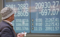 A man looks at an electronic stock board of a securities firm in Tokyo, on March 25, 2019. (AP Photo/Koji Sasahara)