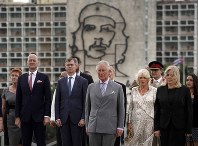 Backdropped by an image of Che Guevara, Britain's Prince Charles, the Prince of Wales, center, and Camilla, Duchess of Cornwall, center right, attend a wreath-laying ceremony at the Jose Marti Monument during their official visit in Havana, Cuba, on March 24, 2019. (AP Photo/Ramon Espinosa)