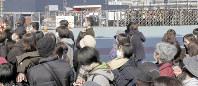 抽選券を求めマツダスタジアム前で列を作るファンら。配布が打ち切られ、球場入り口のゲート(右奥)が閉められた後も多くの人が残った=広島市で2月25日午前11時ごろ