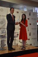 資生堂の魚谷雅彦CEO(左)にサイン入りのスケート靴を手渡すフィギュアスケート女子のアリーナ・ザギトワ=東京都内で2019年3月26日午後5時22分、福田智沙撮影