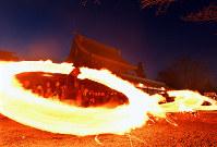 Parishioners swing around burning dried grass tied to ropes in a ritual at Aso Shrine in the city of Aso, Kumamoto Prefecture, on March 24, 2019. (Mainichi/Michiko Morizono)