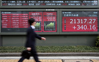 A man walks by an electronic stock board of a securities firm in Tokyo, on March 26, 2019. (AP Photo/Koji Sasahara)