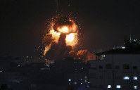 An explosion caused by Israeli airstrikes is seen from the offices of Hamas leader Ismail Haniyeh in Gaza City, on March 25, 2019. (AP Photo/Adel Hana)